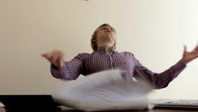 Ο νεαρός άνδρας κάθεται σε ένα γραφείο Ξαφνικά παίρνει τα έγγραφά του και τα ρίχνει στην slo-Mo απόθεμα βίντεο
