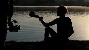 Ο νεαρός άνδρας κάθεται σε μια τράπεζα λιμνών και εξετάζει ένα κύπελλο νικητών στην slo-Mo απόθεμα βίντεο