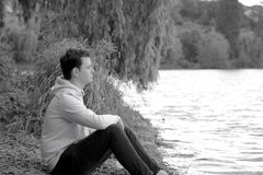 Ο νεαρός άνδρας κάθεται στην άκρη του νερού με ένα πουλόβερ και μια κουκούλα στοκ εικόνες