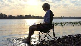 Ο νεαρός άνδρας κάθεται, χαμογελά και κινεί το Barefeet του στο νερό σε ένα Riverbank στην slo-Mo απόθεμα βίντεο