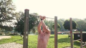 Ο νεαρός άνδρας κάνει τις διάφορες bodyweight ασκήσεις στον οριζόντιο φραγμό φιλμ μικρού μήκους