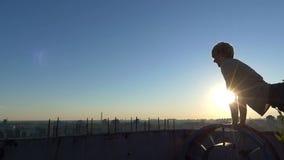 Ο νεαρός άνδρας κάνει το ώθηση-UPS σε ένα τεράστιο cogweel στο ηλιοβασίλεμα στην slo-Mo φιλμ μικρού μήκους