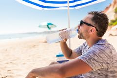 Ο νεαρός άνδρας κάτω από την ηλιακή ομπρέλα πίνει το νερό από το δοχείο ψύξης στην παραλία θάλασσας στοκ φωτογραφίες με δικαίωμα ελεύθερης χρήσης