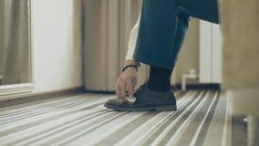Ο νεαρός άνδρας καθαρίζει τα παπούτσια του, κινηματογράφηση σε πρώτο π απόθεμα βίντεο