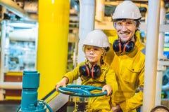 Ο νεαρός άνδρας και ένα μικρό αγόρι είναι και τα δύο σε μια κίτρινη εργασία ομοιόμορφη, τα γυαλιά, και το κράνος σε ένα βιομηχανι στοκ εικόνες