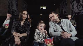 Ο νεαρός άνδρας και η γυναίκα με ένα παιδί προσέχουν έναν κινηματογράφο απόθεμα βίντεο