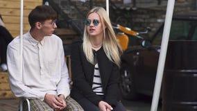 Ο νεαρός άνδρας και η γυναίκα μιλούν καθμένος στην ταλάντευση φιλμ μικρού μήκους