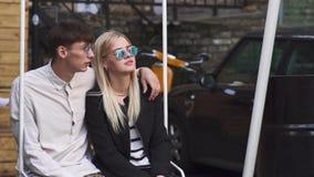 Ο νεαρός άνδρας και η γυναίκα μιλούν καθμένος στην ταλάντευση απόθεμα βίντεο