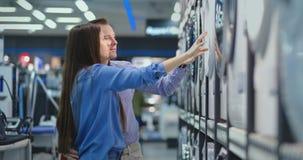 Ο νεαρός άνδρας και η γυναίκα στο κατάστημα συσκευών επιλέγουν να αγορ απόθεμα βίντεο