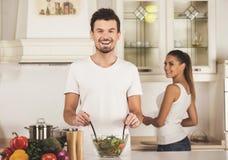 Ο νεαρός άνδρας και η σύζυγός του προετοιμάζουν το γεύμα στην κουζίνα στοκ εικόνα