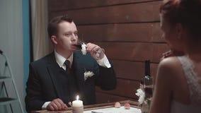 Ο νεαρός άνδρας και το όμορφο κορίτσι του πίνουν το κρασί κατά τη διάρκεια του γεύματος σε ένα εστιατόριο, σε αργή κίνηση φιλμ μικρού μήκους