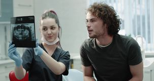Ο νεαρός άνδρας κινηματογραφήσεων σε πρώτο πλάνο στον οδοντίατρο έχει μια φιλική συνομιλία με το γιατρό του, ο νέος οδοντίατρος ε φιλμ μικρού μήκους