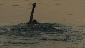 Ο νεαρός άνδρας κολυμπά το ύπτιο σε έναν λαμπιρίζοντας ποταμό τη νύχτα το καλοκαίρι στην slo-Mo φιλμ μικρού μήκους