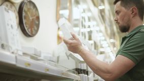 Ο νεαρός άνδρας κρατά δύο ρολόγια τοίχων και επιλέγει μεταξύ τους σε μια υπεραγορά απόθεμα βίντεο