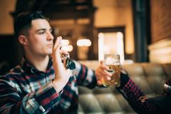 Ο νεαρός άνδρας κρατά τα κλειδιά αυτοκινήτων και αρνείται να πιει την μπύρα από τον αμερικανικό φίλο afro του πίνει το ρυθμιστή ό στοκ εικόνες