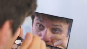 Ο νεαρός άνδρας μαδά τα φρύδια του με τα τσιμπιδάκια μπροστά από τον καθρέφτη στο σπίτι απόθεμα βίντεο