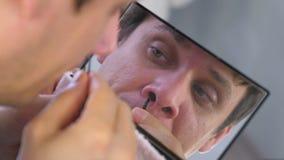 Ο νεαρός άνδρας μαδά τις τρίχες του από τη μύτη με τα τσιμπιδάκια μπροστά από τον καθρέφτη στο σπίτι απόθεμα βίντεο