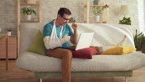 Ο νεαρός άνδρας με έναν σπασμένους βραχίονα και ένα πόδι χρησιμοποιεί ένα lap-top και μαθαίνει για κερδίζει φιλμ μικρού μήκους