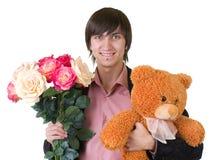 Ο νεαρός άνδρας με τα λουλούδια και teddy αντέχει στοκ εικόνες