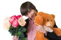 Ο νεαρός άνδρας με τα λουλούδια και teddy αντέχει στοκ φωτογραφία με δικαίωμα ελεύθερης χρήσης