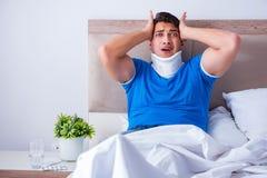 Ο νεαρός άνδρας με τον τραυματισμό λαιμών στο κρεβάτι στοκ φωτογραφίες με δικαίωμα ελεύθερης χρήσης