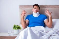 Ο νεαρός άνδρας με τον τραυματισμό λαιμών στο κρεβάτι στοκ εικόνες με δικαίωμα ελεύθερης χρήσης