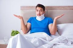 Ο νεαρός άνδρας με τον τραυματισμό λαιμών στο κρεβάτι στοκ φωτογραφία με δικαίωμα ελεύθερης χρήσης