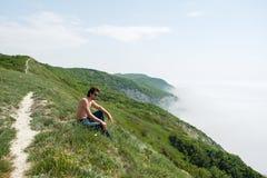 Ο νεαρός άνδρας με το γυμνό κορμό στα τζιν και τα γυαλιά κάθεται στην άκρη ενός απότομου βράχου και εξετάζει την ομίχλη Στοκ Εικόνα