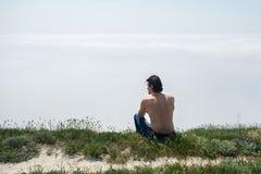 Ο νεαρός άνδρας με το γυμνό κορμό στα τζιν και τα γυαλιά κάθεται στην άκρη ενός απότομου βράχου και εξετάζει την ομίχλη Στοκ Εικόνες