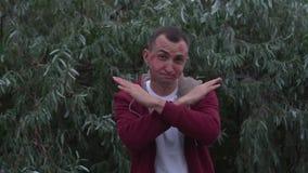 Ο νεαρός άνδρας με το σύνολο προσώπου των σημαδιών κραγιόν των φιλιών παρουσιάζει χειρονομία σημαδιών στάσεων με το πέρασμα των χ απόθεμα βίντεο