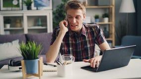Ο 0 νεαρός άνδρας μιλά στο κινητό τηλέφωνο και χρησιμοποιεί το lap-top εκφράζοντας την ενόχληση και την οργή εργαζόμενος σύγχρονο απόθεμα βίντεο