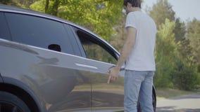Ο νεαρός άνδρας μπορεί ` τ ανοίγει μια πόρτα του σύγχρονου αυτοκινήτου φιλμ μικρού μήκους