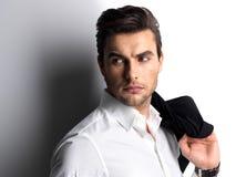 Ο νεαρός άνδρας μόδας στο άσπρο πουκάμισο κρατά το μαύρο σακάκι Στοκ εικόνες με δικαίωμα ελεύθερης χρήσης