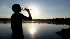 Ο νεαρός άνδρας πίνει το νερό από ένα πλαστικό μπουκάλι στο ηλιοβασίλεμα φιλμ μικρού μήκους
