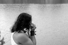 Ο νεαρός άνδρας παίζει υπαίθριο τον κοντινό φυσαρμόνικων μόνο η λίμνη Στοκ Εικόνες