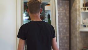 Ο νεαρός άνδρας παίρνει έξω το γάλα από το ψυγείο απόθεμα βίντεο
