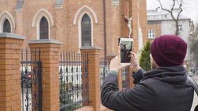 Ο νεαρός άνδρας παίρνει μια φωτογραφία της εκκλησίας με μια ταμπλέτα απόθεμα βίντεο