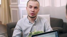 Ο νεαρός άνδρας παίρνει συνέντευξη από για την εργασία στο θηλυκό διευθυντή στην αρχή απόθεμα βίντεο