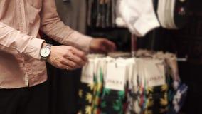 Ο νεαρός άνδρας περιστρέφεται γύρω από το ράφι με τις κάλτσες, που παίρνουν ένα ζευγάρι στα χέρια, κινηματογράφηση σε πρώτο πλάνο απόθεμα βίντεο