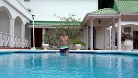 Ο νεαρός άνδρας πηγαίνει στην πισίνα απόθεμα βίντεο