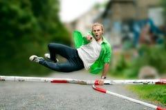 Ο νεαρός άνδρας πηδά πέρα από ένα εμπόδιο Στοκ Εικόνες