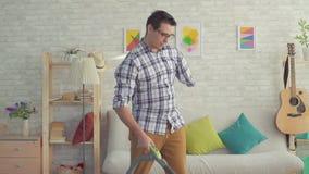Ο νεαρός άνδρας πορτρέτου που τίθεται εκτός λειτουργίας χωρίς ένα χέρι καθαρίζει το σπίτι με ένα αργό MO ηλεκτρικών σκουπών φιλμ μικρού μήκους