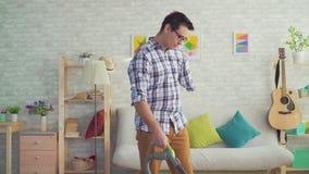 Ο νεαρός άνδρας πορτρέτου που τίθεται εκτός λειτουργίας χωρίς ένα χέρι καθαρίζει το σπίτι με μια ηλεκτρική σκούπα φιλμ μικρού μήκους