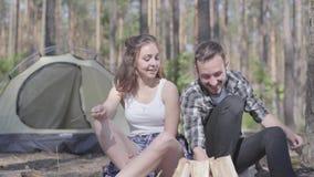 Ο νεαρός άνδρας που ανάβει μια πυρκαγιά στο δάσος ενώ αρκετά νέα συνεδρίαση γυναικών πλησίον Αγαπώντας ζεύγος που στηρίζεται υπαί απόθεμα βίντεο
