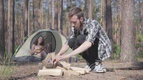 Ο νεαρός άνδρας που ανάβει μια πυρκαγιά στο πρώτο πλάνο στο δάσος ενώ αρκετά νέα γυναίκα που παίζει ukulele στο υπόβαθρο απόθεμα βίντεο