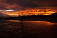 Ο νεαρός άνδρας που αυξάνεται παραδίδει τον αέρα επειδή είναι ευχαριστημένος, από ένα ηλιοβασίλεμα colorfull στο υπόβαθρο στην πα στοκ εικόνες
