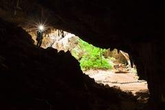 Ο νεαρός άνδρας που εξερευνά τη σπηλιά μυστηρίου με έναν φανό, σπηλιά Phraya Nakhon είναι μια μεγάλη σπηλιά που έχει μια τρύπα στ στοκ φωτογραφίες με δικαίωμα ελεύθερης χρήσης