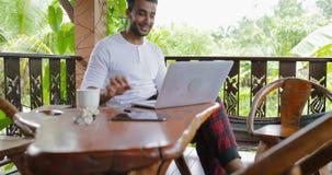 Ο νεαρός άνδρας που εργάζεται με το φορητό προσωπικό υπολογιστή στο πεζούλι πίνει τον καφέ, ισπανική δακτυλογράφηση τύπων που κου απόθεμα βίντεο
