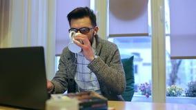 Ο νεαρός άνδρας που εργάζεται στο lap-top και πίνει τον καφέ απόθεμα βίντεο