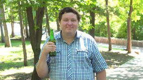 Ο νεαρός άνδρας που κρατά μια μπύρα και λέει ναι με το τίναγμα επικεφαλής, υπαίθριος απόθεμα βίντεο